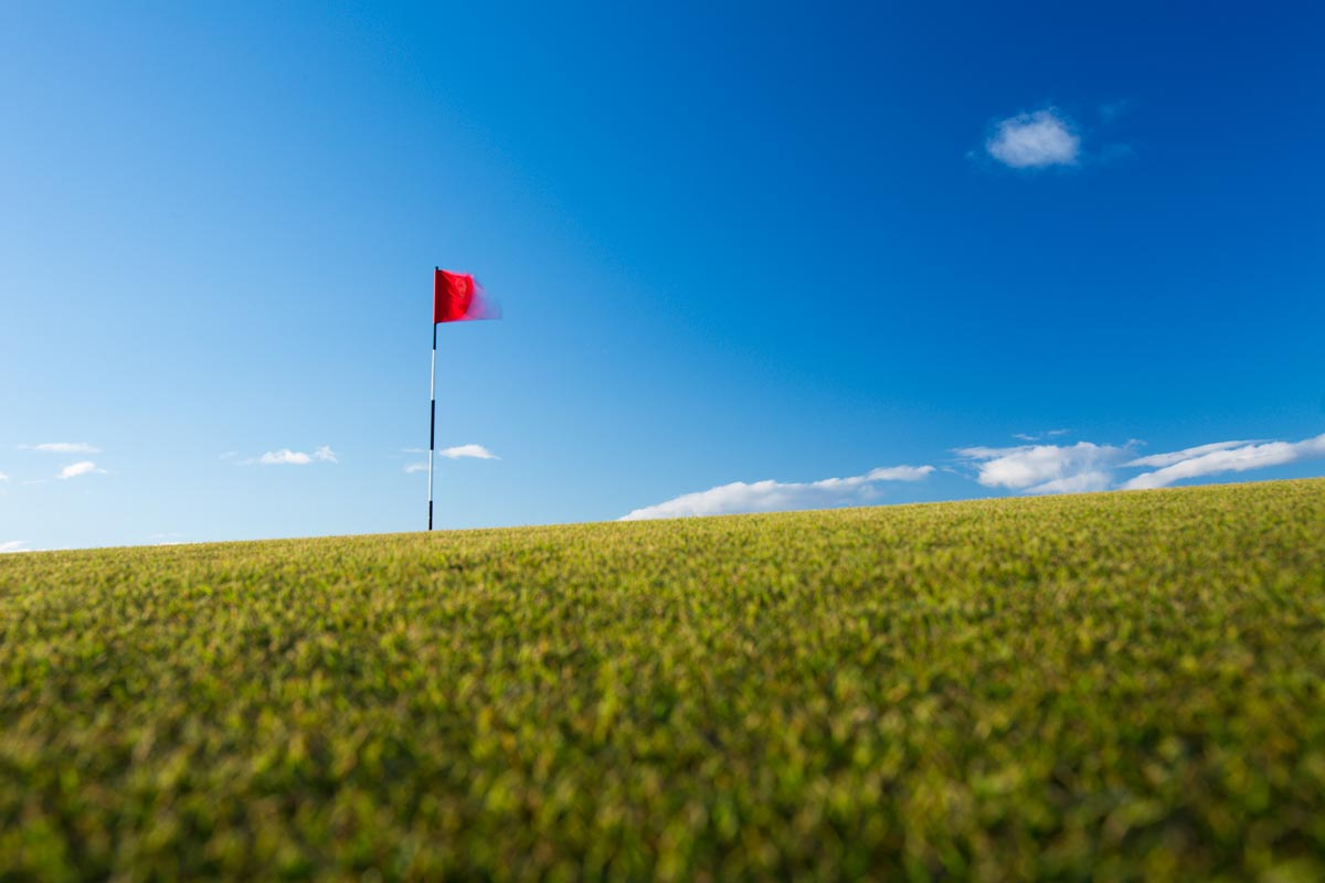 Red Golf Flag On A Golf Course, Moving In The Wind (motion Blurr